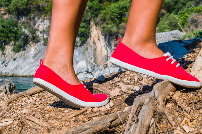 Ciérrese para arriba de los pies de una muchacha del turista que llevan los zapatos rojos que caminan en la isla del cefalonia, m imagenes de archivo
