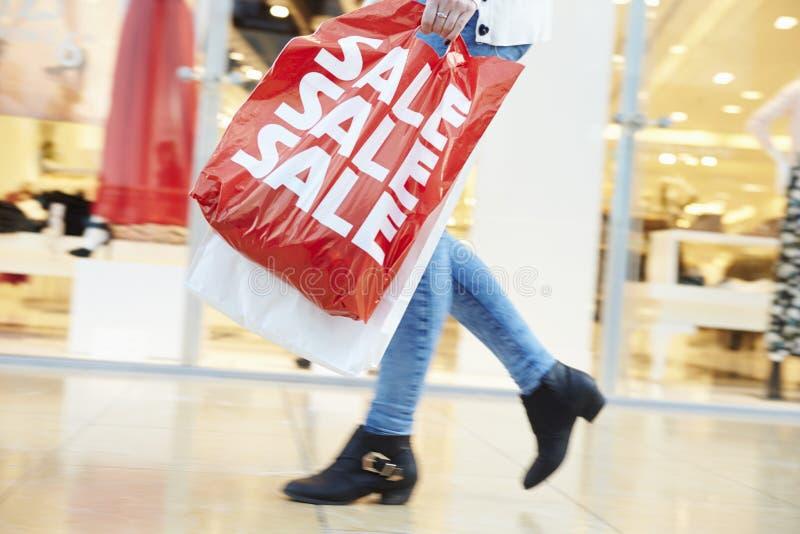 Ciérrese para arriba de los pies del comprador que llevan bolsos en alameda de compras imagen de archivo
