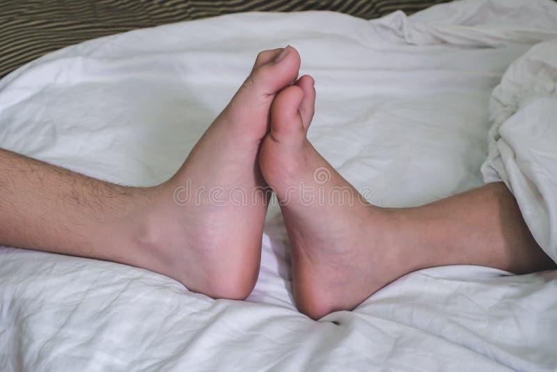 Ciérrese para arriba de los pies masculinos y femeninos en una cama y un par que tienen sexo foto de archivo libre de regalías