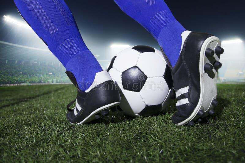 Ciérrese para arriba de los pies que golpean el balón de fútbol con el pie, noche en el estadio imagen de archivo