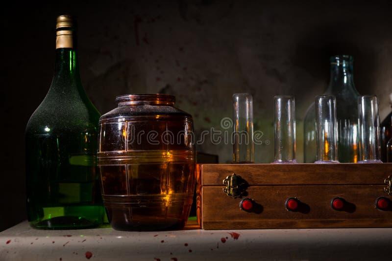 Ciérrese para arriba de los tarros y de las botellas de cristal con la pared salpicada sangre imagen de archivo libre de regalías