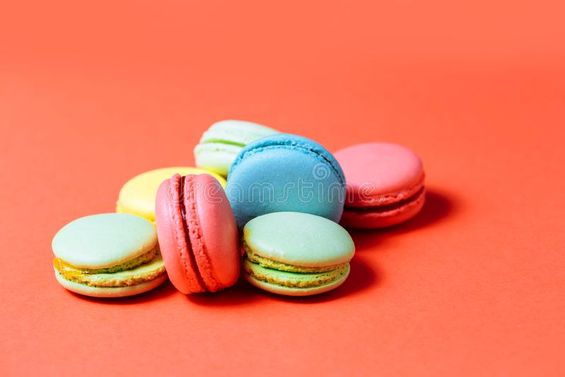 Ciérrese para arriba de macarrones verdes, amarillos, coralinos, azules dulces en fondo rojo Pasteles frescos, desayuno, café imagen de archivo