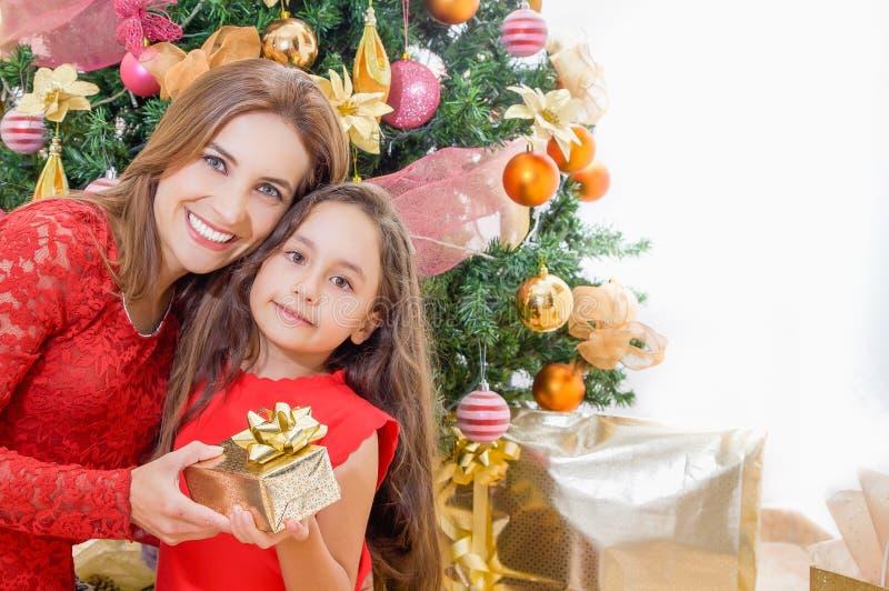 Ciérrese para arriba de mamá feliz y de la hija que sostienen un regalo delante de un árbol de navidad, concepto de la Navidad imagen de archivo libre de regalías