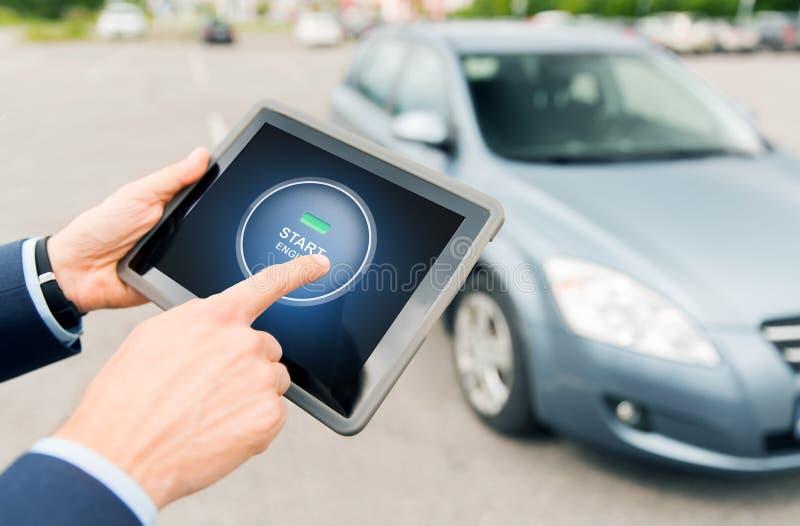 Ciérrese para arriba de manos con el arrancador del coche en la PC de la tableta imágenes de archivo libres de regalías