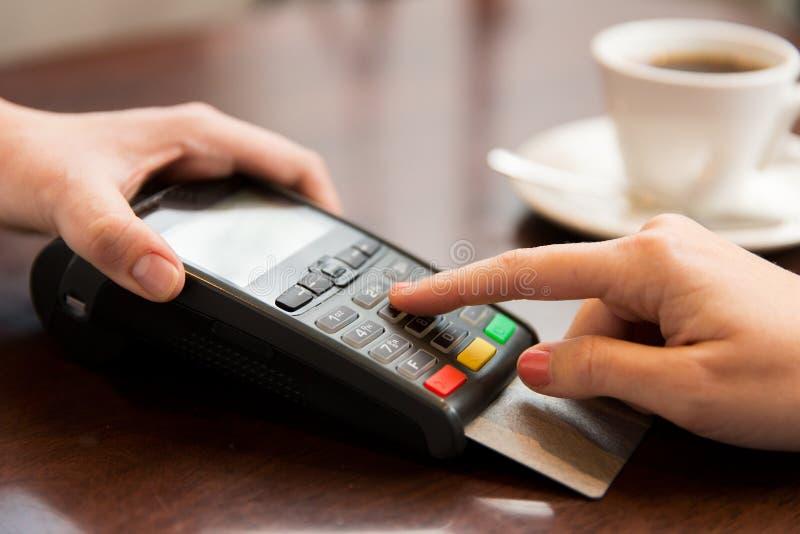 Ciérrese para arriba de manos con el lector de la tarjeta de crédito en el café foto de archivo libre de regalías