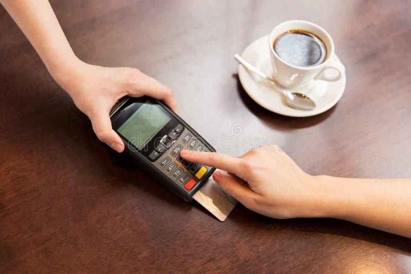Ciérrese para arriba de manos con el lector de la tarjeta de crédito en el café fotografía de archivo