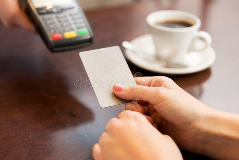 Ciérrese para arriba de manos con el lector de la tarjeta de crédito en el café fotos de archivo