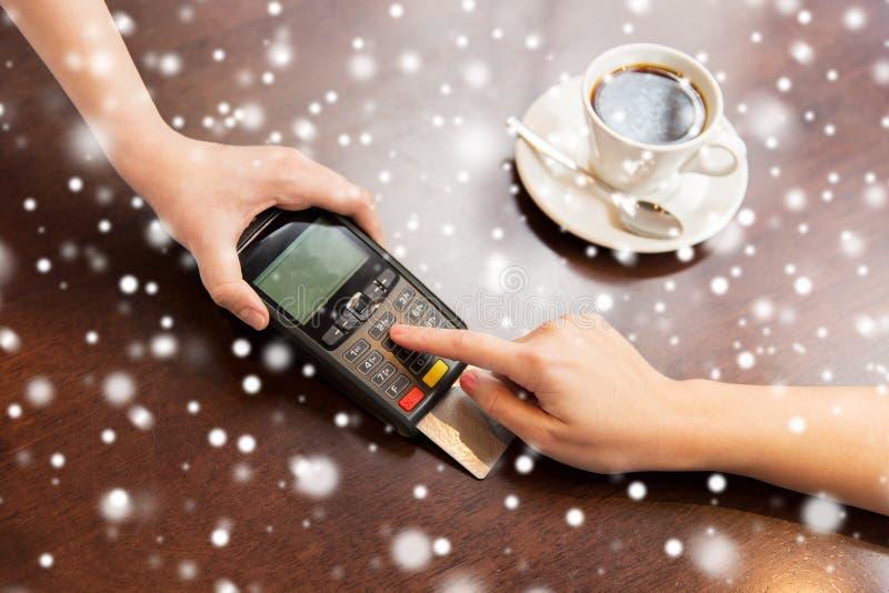Ciérrese para arriba de manos con el lector de la tarjeta de crédito en el café imágenes de archivo libres de regalías