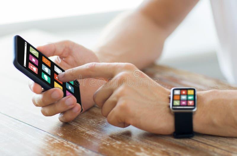 Ciérrese para arriba de manos con el teléfono y el reloj elegantes imagen de archivo libre de regalías