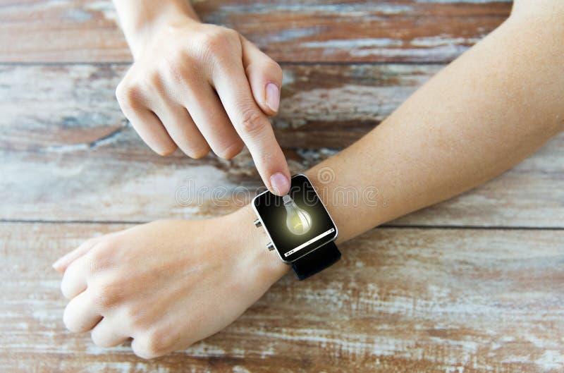 Ciérrese para arriba de manos con la bombilla en el reloj elegante imagenes de archivo