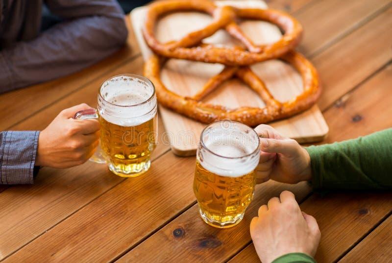 Ciérrese para arriba de manos con las tazas de cerveza en la barra o el pub foto de archivo