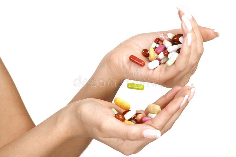 Ciérrese para arriba de manos femeninas con muchas píldoras foto de archivo libre de regalías