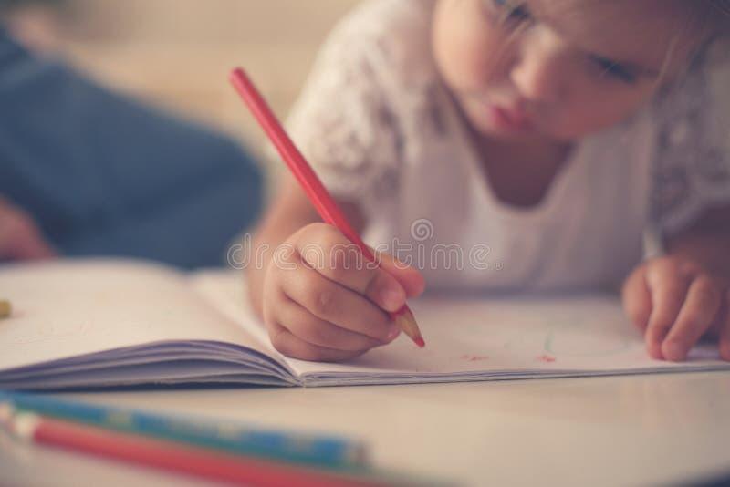 Ciérrese para arriba de manos miman a una niña que escribe junto foto de archivo libre de regalías