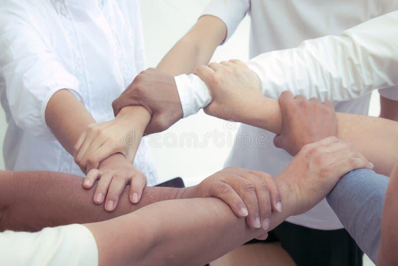 Ciérrese para arriba de manos que se unen a del hombre de negocios en fondo de proceso cruzado de la unidad imagen de archivo