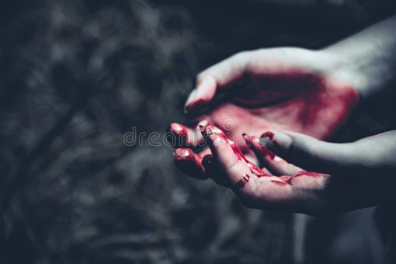 Ciérrese para arriba de manos sangrientas en fondo oscuro del bosque Horror y g imagen de archivo libre de regalías