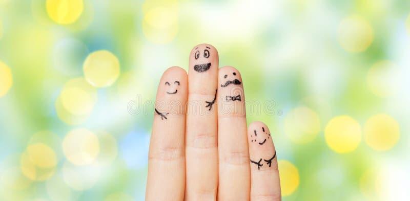 Ciérrese para arriba de manos y de fingeres con las caras sonrientes imágenes de archivo libres de regalías