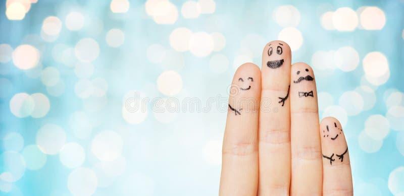 Ciérrese para arriba de manos y de fingeres con las caras sonrientes fotos de archivo