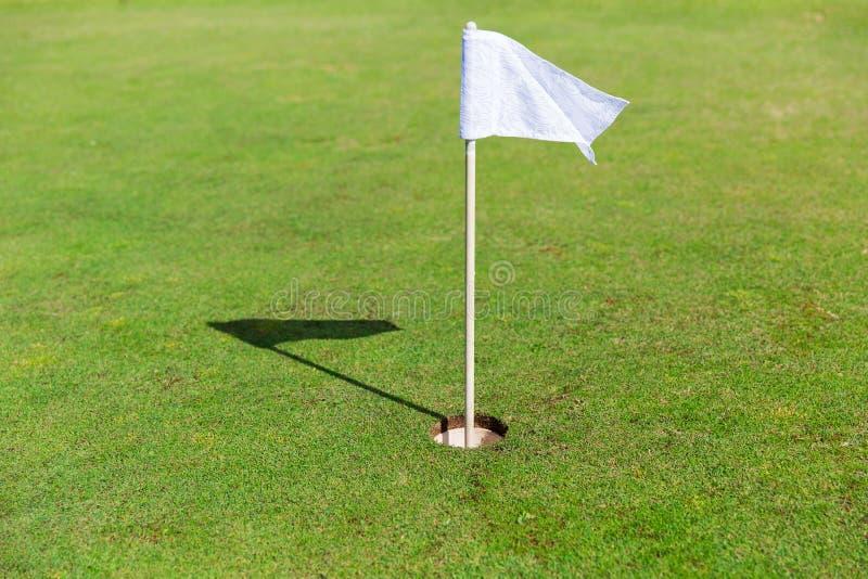 Ciérrese para arriba de marca de la bandera en agujero en campo del golf fotos de archivo