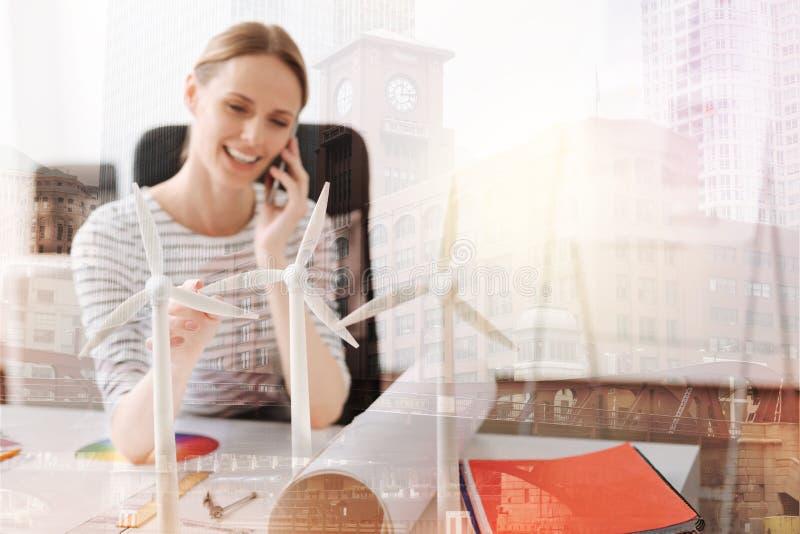 Ciérrese para arriba de modelos de las turbinas de viento en la tabla de un ingeniero de sexo femenino imágenes de archivo libres de regalías