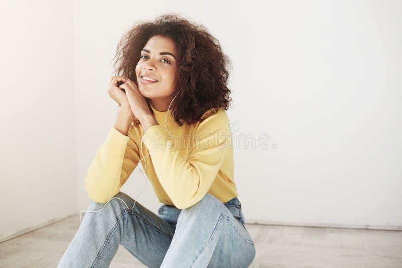 Ciérrese para arriba de muchacha africana alegre apuesta joven con el peinado rizado retro en cuello alto y vintage amarillos ele fotos de archivo libres de regalías