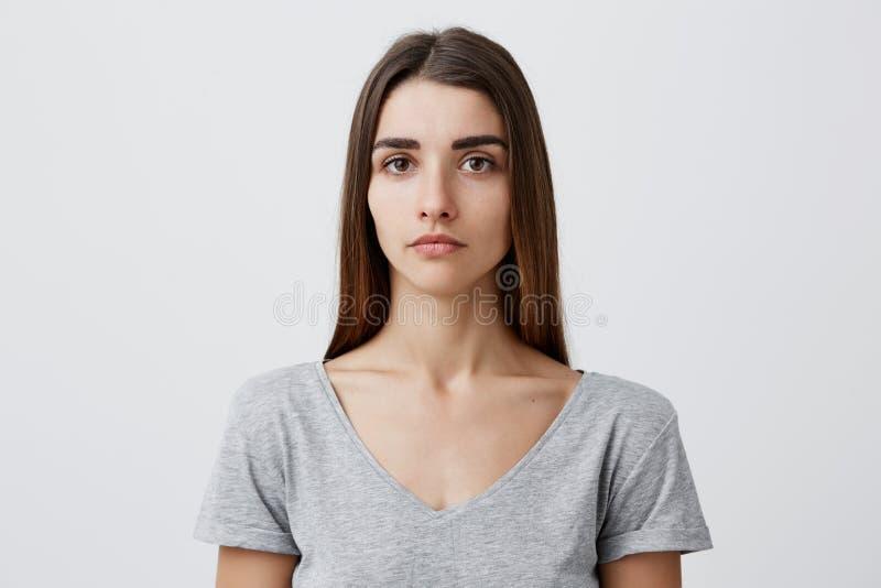 Ciérrese para arriba de muchacha caucásica encantadora hermosa joven con el pelo marrón largo en la camiseta gris que mira in cam imagen de archivo libre de regalías