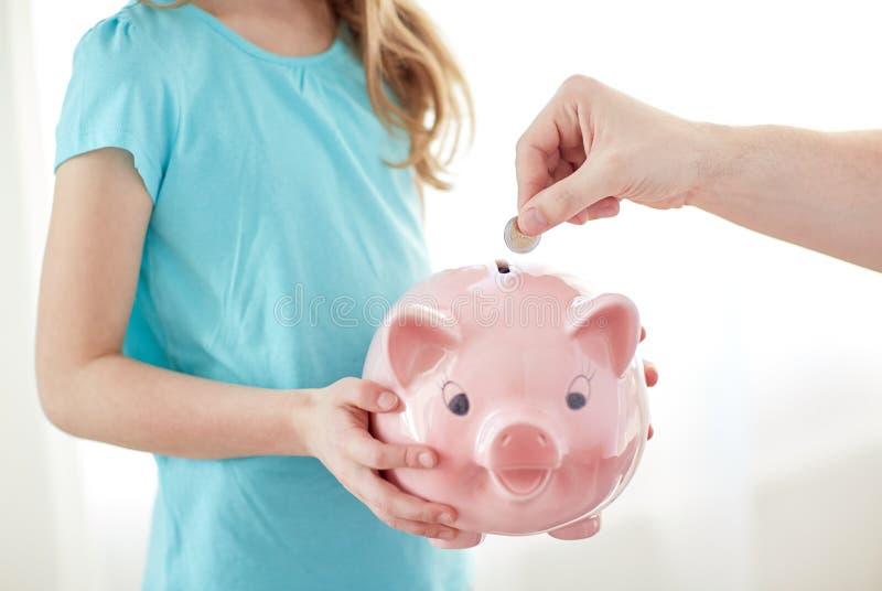 Ciérrese para arriba de muchacha con la hucha que pone la moneda imagen de archivo libre de regalías