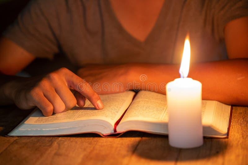 Ciérrese para arriba de muchachos cristianos son biblia de la lectura y del estudio en el cuarto y velas encendidas a la luz, con foto de archivo libre de regalías