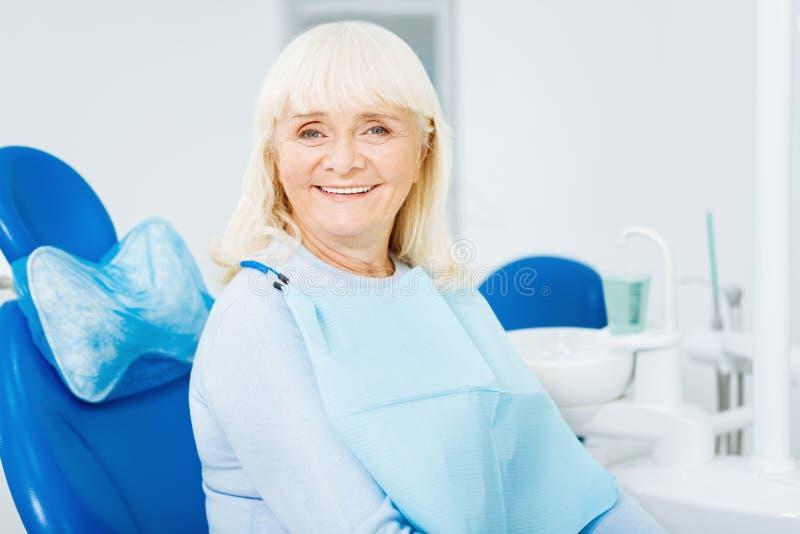 Ciérrese para arriba de mujer alegre en oficina dental foto de archivo