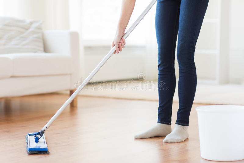 Ciérrese para arriba de mujer con el piso de la limpieza de la fregona en casa foto de archivo libre de regalías
