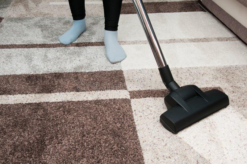 Ciérrese para arriba de mujer con la alfombra de la limpieza del aspirador de las piernas en casa imágenes de archivo libres de regalías
