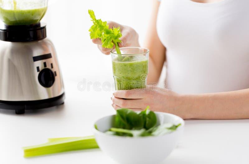 Ciérrese para arriba de mujer con la licuadora y el smoothie verde imagen de archivo