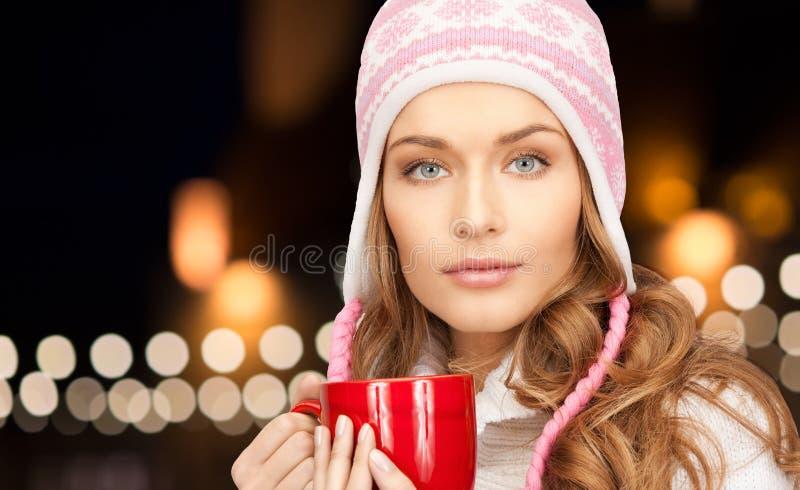 Ciérrese para arriba de mujer con la taza sobre luces de la Navidad imágenes de archivo libres de regalías