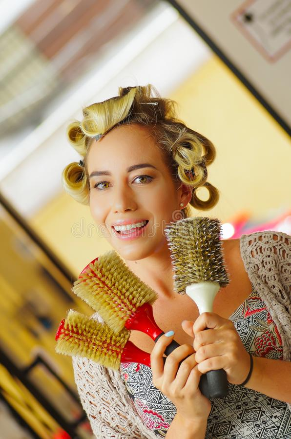 Ciérrese para arriba de mujer en el peluquero, sosteniendo en sus manos muchos cepillos de la ronda, en un salón de pelo fotografía de archivo libre de regalías
