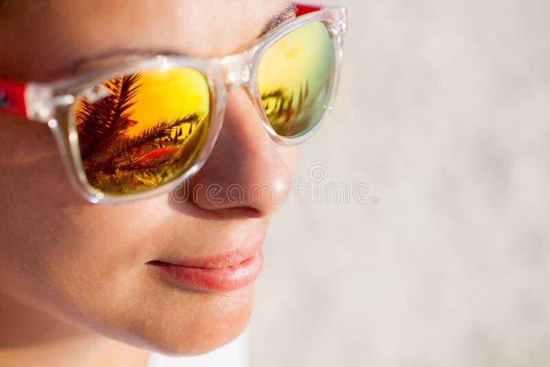 Ciérrese para arriba de mujer en gafas de sol con la reflexión de la playa imagen de archivo