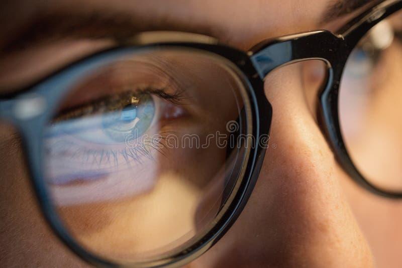 Ciérrese para arriba de mujer en los vidrios que miran la pantalla foto de archivo