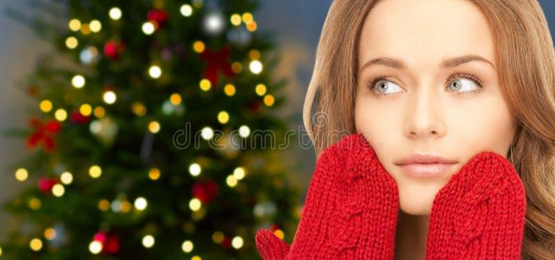 Ciérrese para arriba de mujer en manoplas sobre el árbol de navidad fotos de archivo