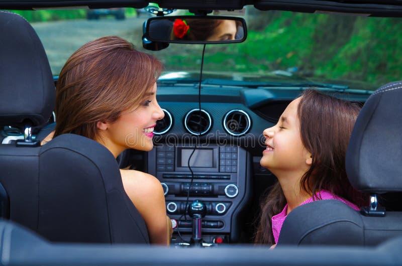 Ciérrese para arriba de mujer hermosa y su del daugher magnífico que llevan un vestido rosado que presenta dentro de un coche neg foto de archivo