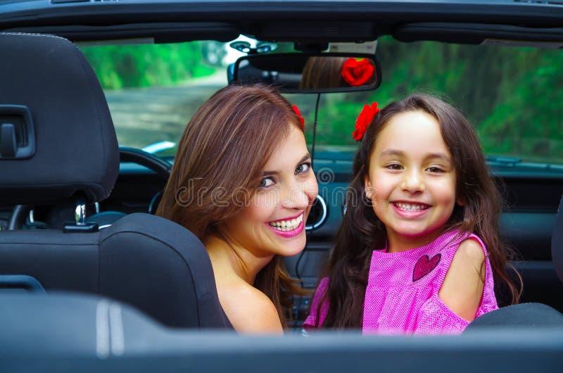 Ciérrese para arriba de mujer hermosa y su del daugher magnífico que llevan un vestido rosado que presenta dentro de un coche neg imagen de archivo