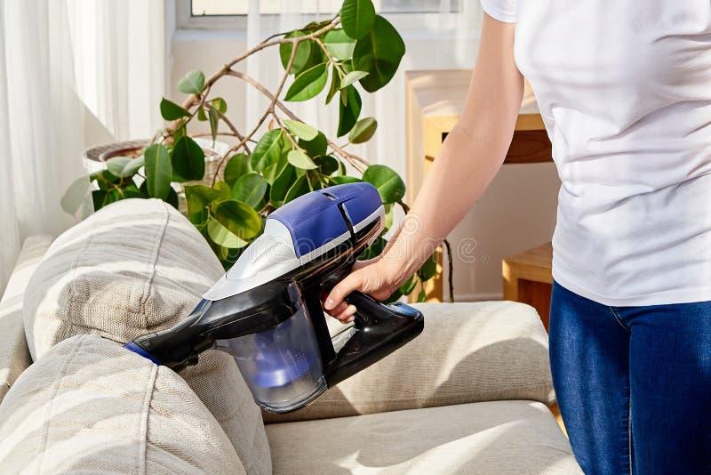 Ciérrese para arriba de mujer joven en el sofá blanco de la camisa y de la limpieza de los vaqueros con el aspirador en casa, esp imagen de archivo