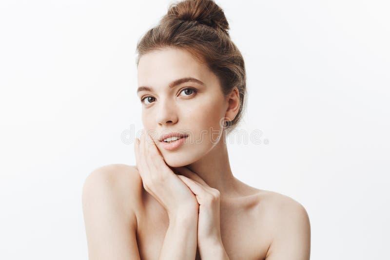 Ciérrese para arriba de mujer joven oscuro-cabelluda atractiva con el peinado del bollo y los hombros desnudos que llevan a cabo  imagen de archivo