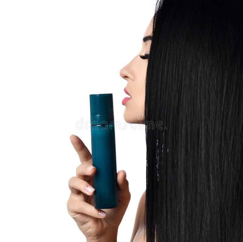 Ciérrese para arriba de mujer morena atractiva en perfil con el pelo recto que huele de goce de la botella de perfume en blanco C fotos de archivo