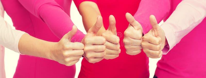 Ciérrese para arriba de mujeres en las camisas rosadas que muestran los pulgares para arriba foto de archivo libre de regalías