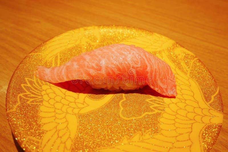 Ciérrese para arriba de nigiri del sushi del atún del otoro en la placa en el restaurante de Japón de la correa del sushi foto de archivo