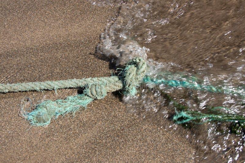 Ciérrese para arriba de nudo de la cuerda en la playa de la arena Una onda apacible está viniendo S imagen de archivo