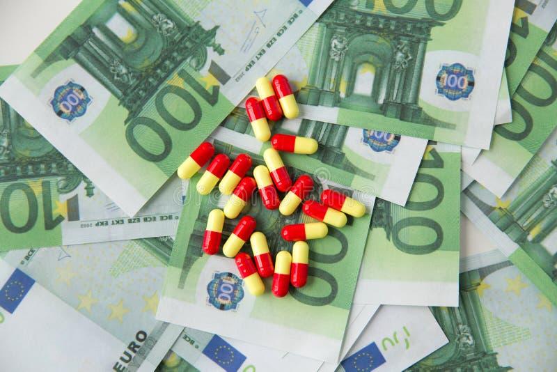 Ciérrese para arriba de píldoras o las drogas y dinero euro del efectivo imágenes de archivo libres de regalías