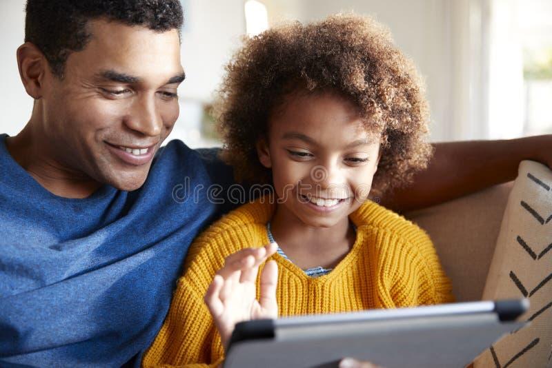 Ciérrese para arriba de padre y de la hija que usa la tableta junto, sentándose en el sofá en la sala de estar, foco selectivo fotos de archivo