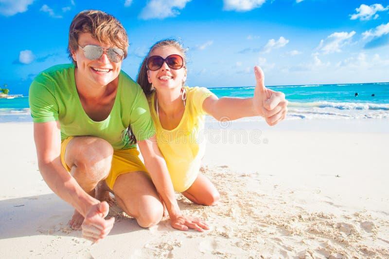 Ciérrese para arriba de pares caucásicos jovenes felices en las gafas de sol que sonríen en la playa imagenes de archivo