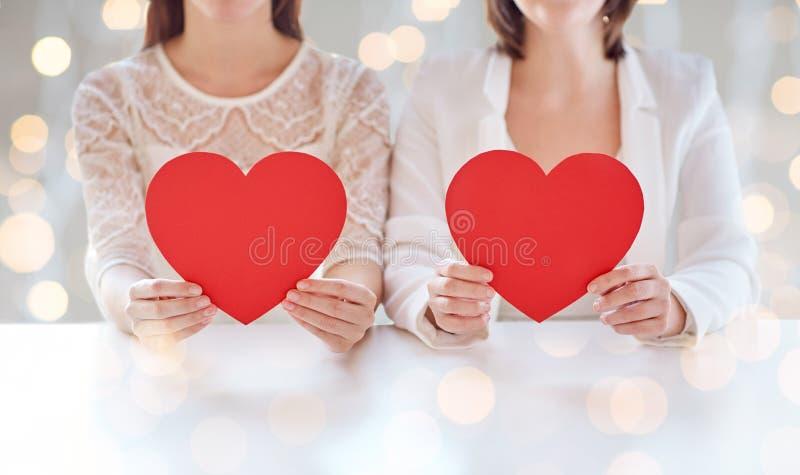 Ciérrese para arriba de pares lesbianos felices con los corazones rojos imagenes de archivo