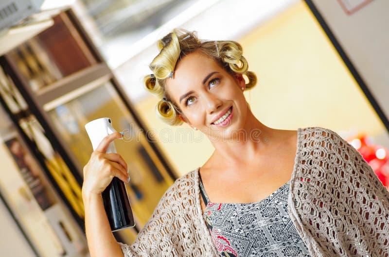 Ciérrese para arriba de peinado de la fijación de la mujer joven con la laca para el pelo en salón de belleza de la peluquería imagenes de archivo