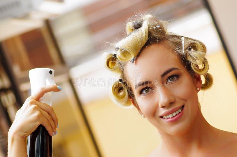 Ciérrese para arriba de peinado de la fijación de la mujer joven con la laca para el pelo en salón de belleza de la peluquería, e imagenes de archivo